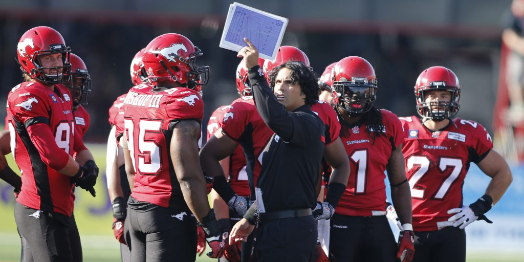 Calgary Stampeders' special teams coach Mark Kilam, wearing black, goes over plays during second half CFL action against the Ottawa RedBlacks in Calgary, Alberta on Saturday, Aug. 9, 2014.  (CFL PHOTO - Larry MacDougal)