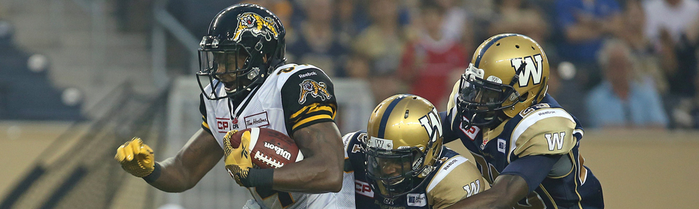Hamilton Tiger-Cats WR Bakari Grant makes a catch under pressure from Winnipeg Blue Bombers DB Maurice Leggett (middle) and DB Bruce Johnson during third quarter CFL action in Winnipeg on Thursday, July 2, 2015. (CFL PHOTO - Jason Halstead)